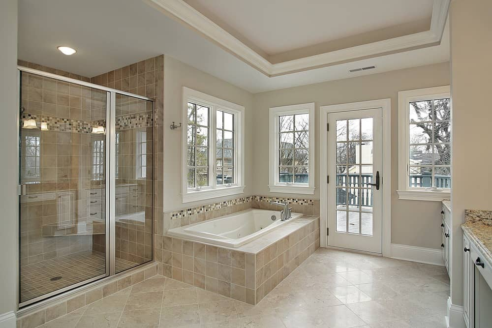 A spacious primary bathroom featuring brown tiles flooring and a tray ceiling. It offers a deep soaking tub, sink counters and a walk-in shower with brown tiles walls.