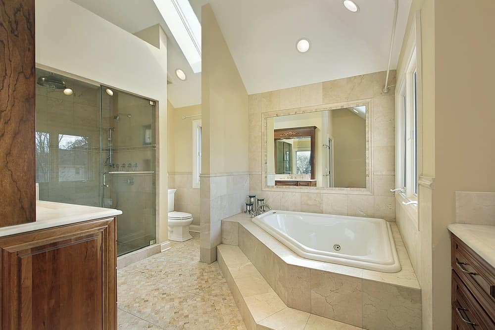 This primary bathroom offers a drop-in soaking tub, sink counters and a large walk-in shower. The room has a tall ceiling with a skylight.