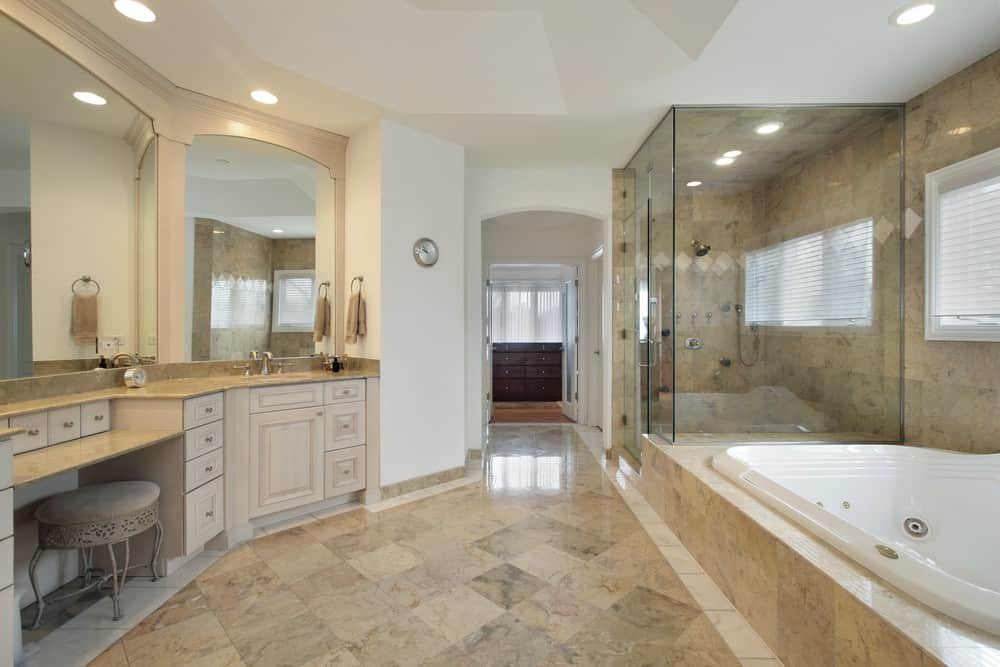 Large primary bathroom with tiles flooring and walls. It has a powder desk, two sink counters, a deep soaking tub and a walk-in shower area.