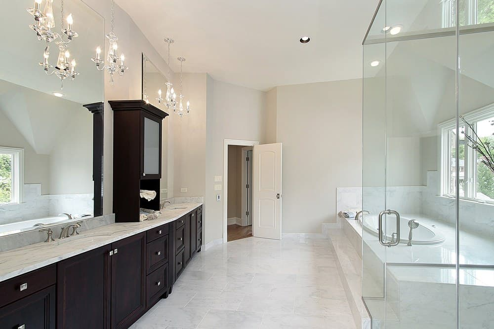Large primary bathroom featuring tiles flooring and a tall ceiling. It also has a long sink counter with two sinks and is lighted by charming chandeliers. The room also has a drop-in tub and a walk-in shower room.