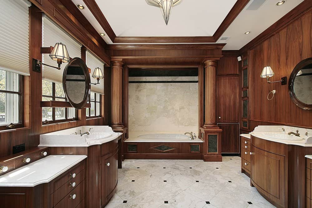 A brown primary bathroom with a rich and classy wood tone. It has a stunning tray ceiling and an elegant drop-in tub. It also has two sink counters.