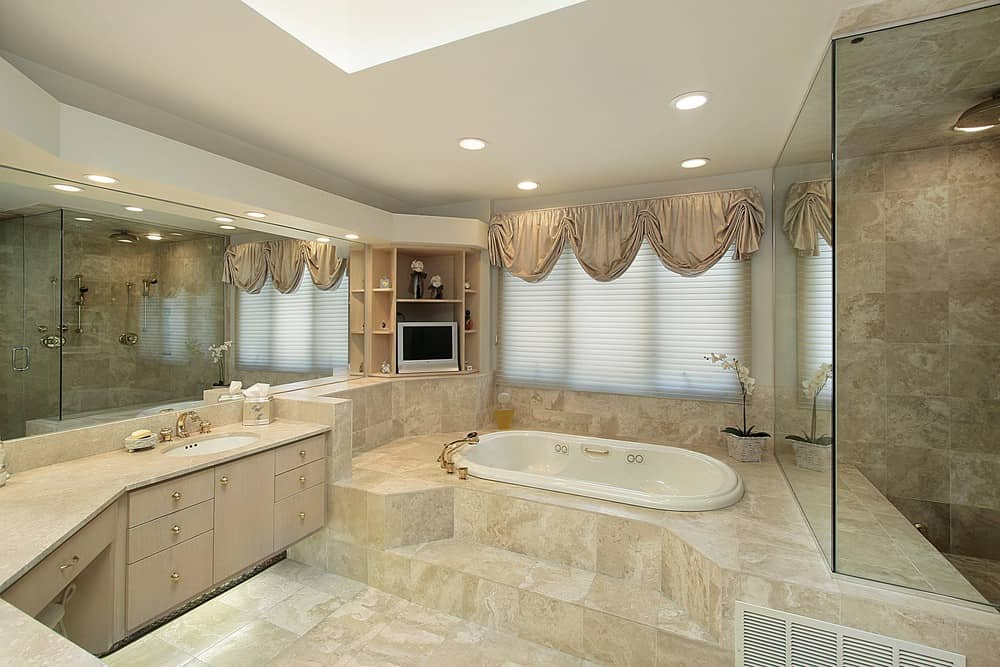 Large primary bathroom with a drop-in soaking tub on a tiles platform along with a large walk-in shower room. There's a built-in shelving as well.