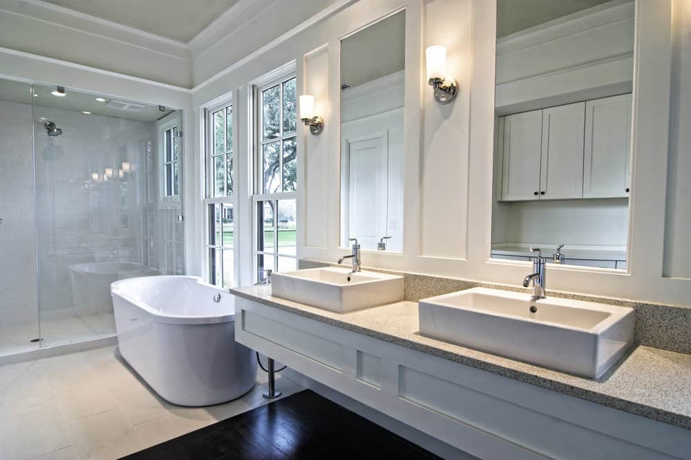 A focused shot at this primary bathroom's floating vanity with two vessel sinks lighted by wall sconces. There's a freestanding soaking tub and a walk-in shower room as well.