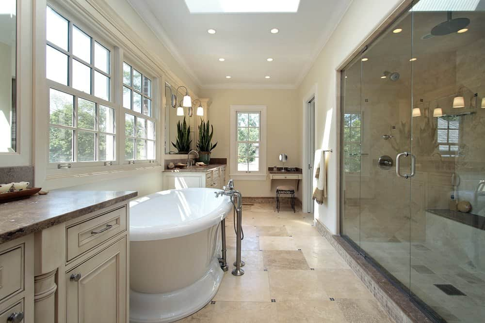 Large primary bathroom featuring two sink counters, a separate powder desk, a large freestanding tub and a large walk-in shower room. The room features a skylight too.
