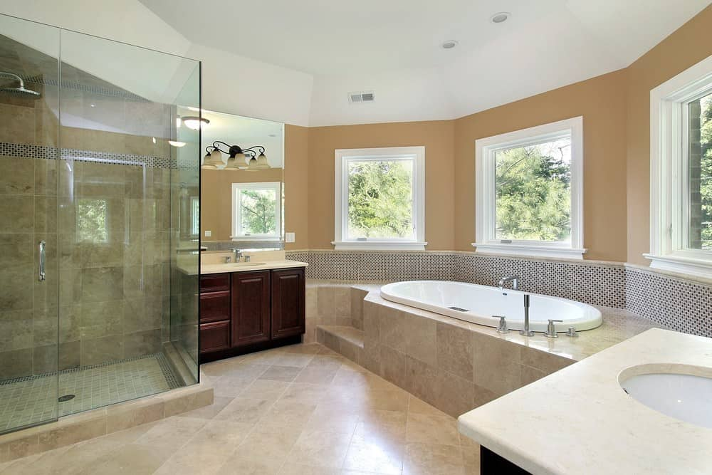 Large primary bathroom featuring two sink counters lighted by wall lights, a drop-in tub, and a walk-in shower room.