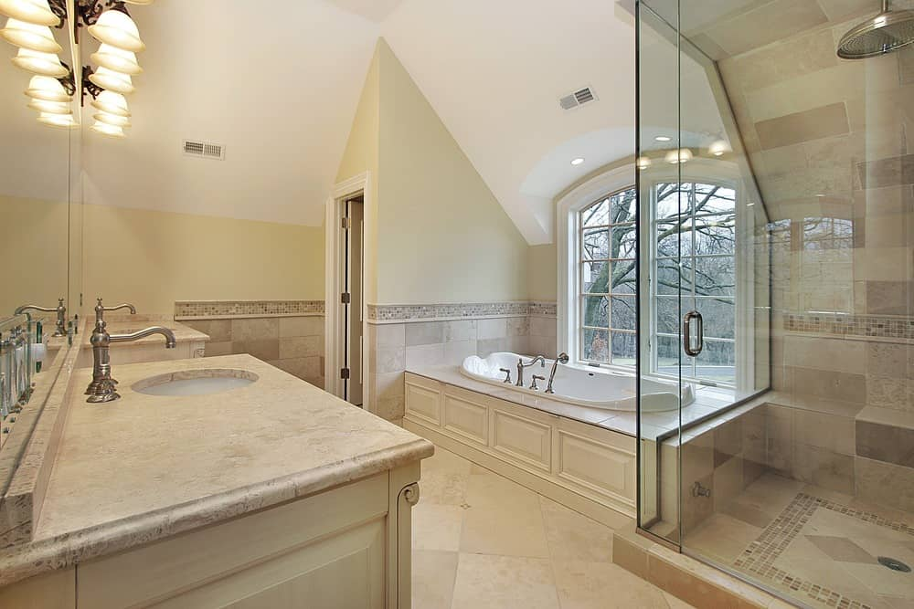 Primary bathroom featuring a tall ceiling and beige tiles flooring. It offers two sink counters, a walk-in shower room and a drop-in tub beside the windows.