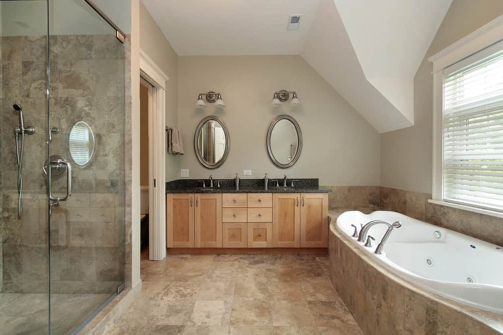 A spacious primary bathroom featuring a black sink counter with two sinks, a drop-in soaking tub, a walk-in shower room and a toilet room.