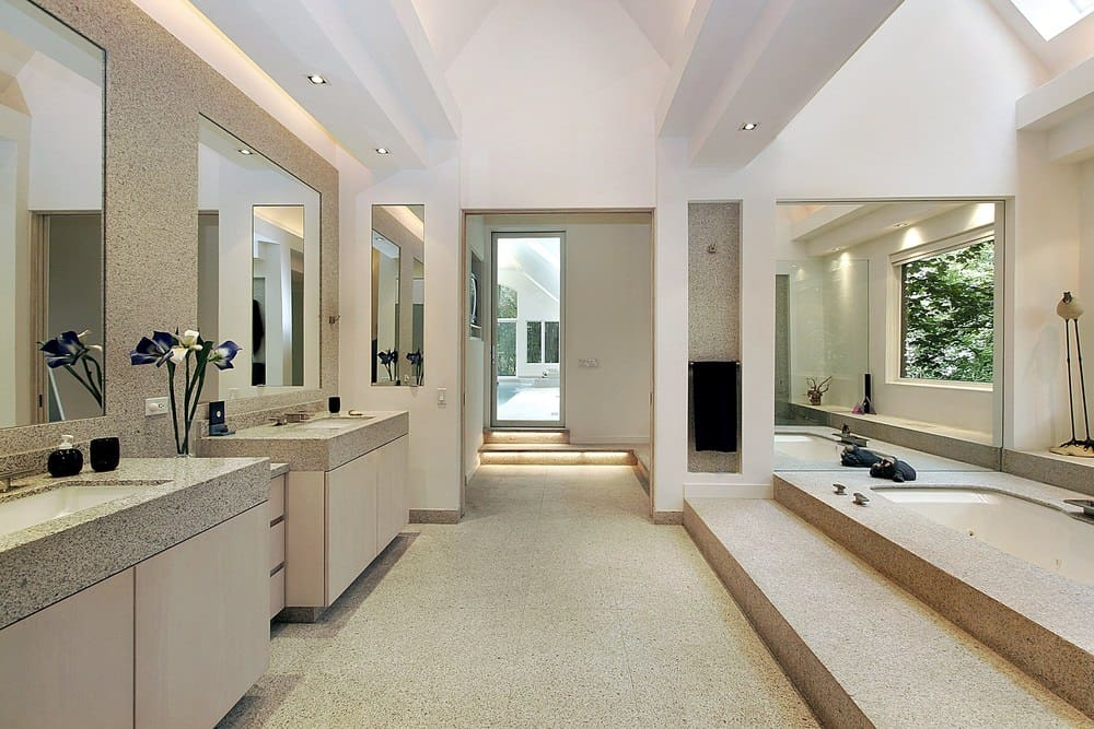 Large primary bathroom with a tall ceiling and tiles flooring. It has two sink counters that look very stylish along with a drop-in tub and a large walk-in shower room.