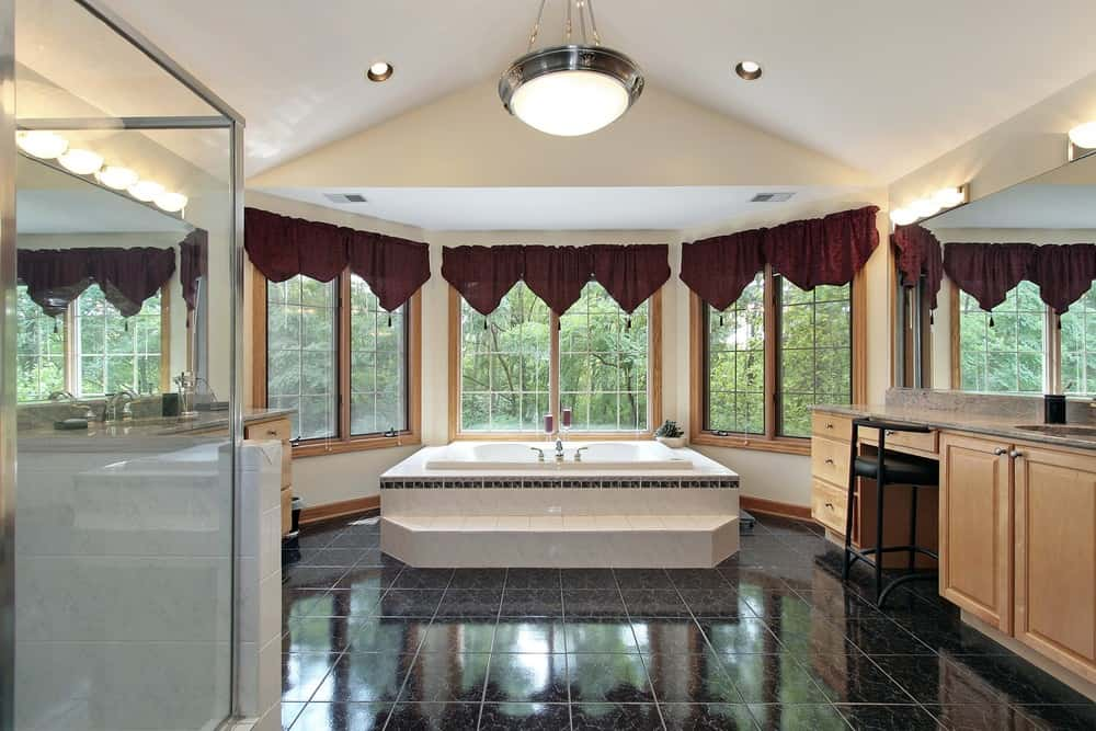 A beautiful primary bathroom boasting black tiles flooring. There's a sink counter, a powder desk, a walk-in shower room and a drop-in tub near the windows.