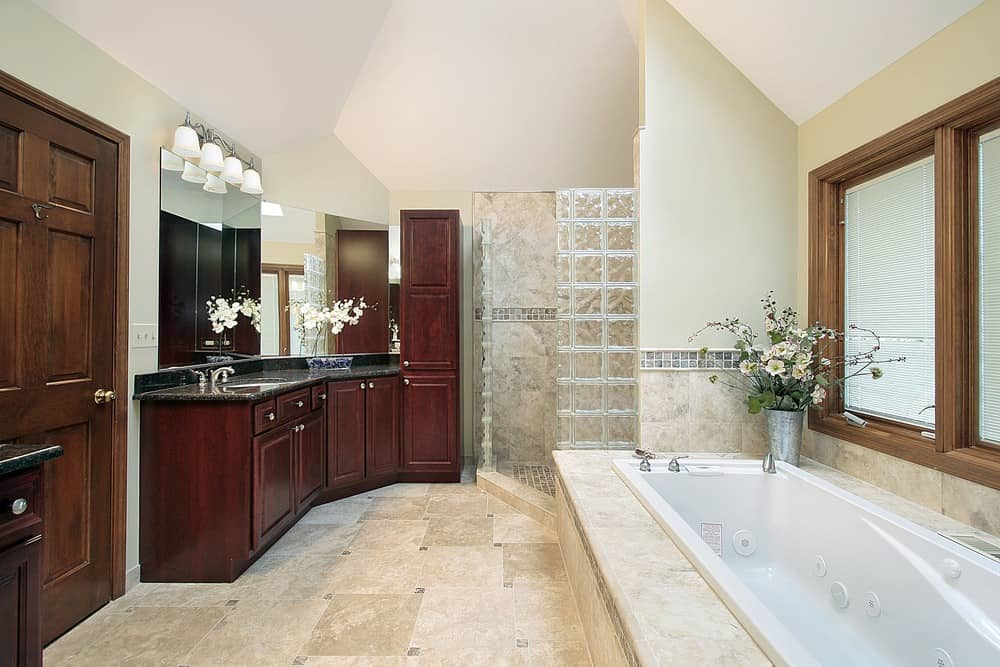 Primary bathroom featuring a black sink counter, a drop-in soaking tub and a walk-in corner shower room.