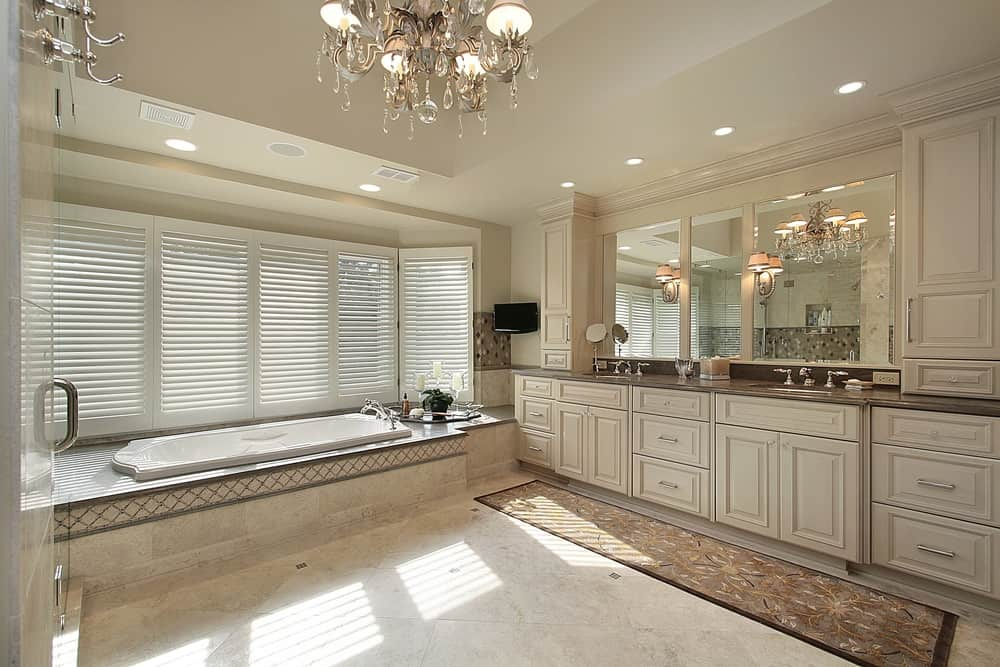 A spacious primary bathroom lighted by a glamorous chandelier. The room offers a sink counter with two sinks, a drop-in soaking tub and a walk-in shower room.