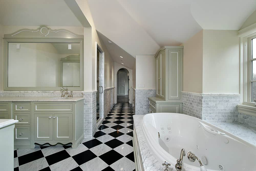 Large primary bathroom with checkered tiles flooring and a tall ceiling. It has a drop-in soaking tub and a large walk-in shower room.