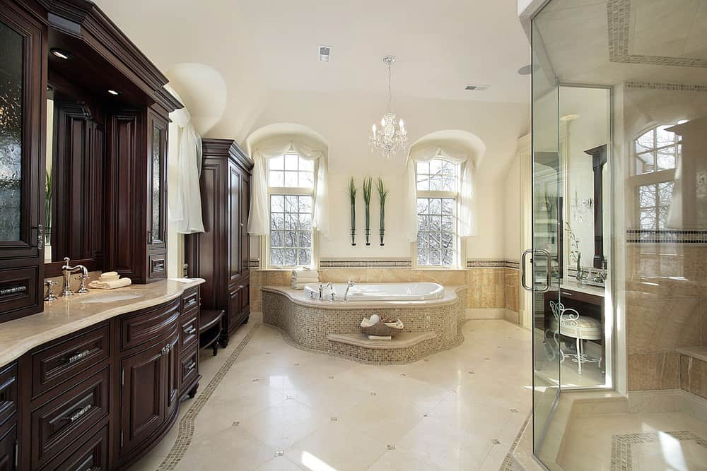 A classy primary bathroom featuring a walk-in corner shower room and a drop-in soaking tub lighted by a charming small chandelier. There's also a powder desk on the side.