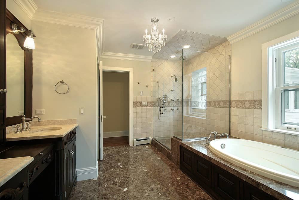 A spacious primary bathroom lighted by a fancy chandelier. The flooring looks absolutely stylish. The room has a drop-in soaking tub and a large walk-in shower room.