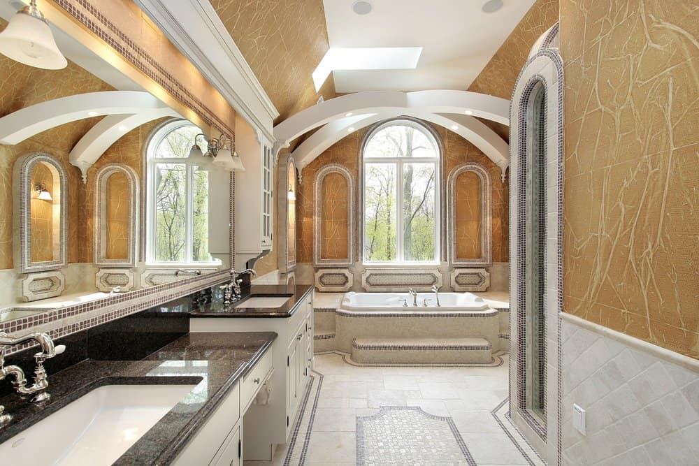 A stunning primary bathroom with decorated brown walls and ceiling. The drop-in tub's design is absolutely amazing. There's a powder desk in between two sink counters. There's also a large walk-in shower room.