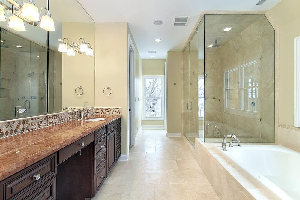 Large primary bathroom boasting a beautiful sink counter lighted by classy wall lights. There's a drop-in soaking tub and a walk-in shower room.