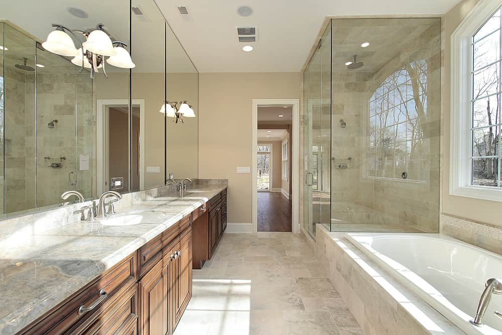 This primary bathroom features a drop-in soaking tub and a long sink counter lighted by wall lights. The room also has a large walk-in shower area.