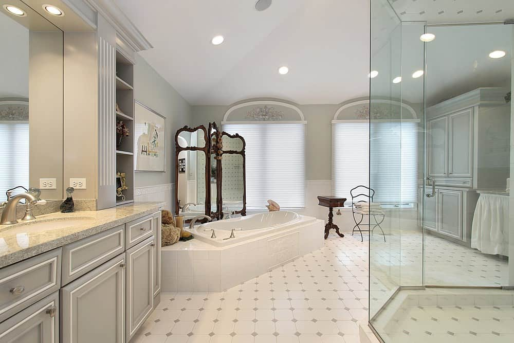 A spacious primary bathroom featuring classy tiles flooring and a tall ceiling. There's a drop-in corner soaking tub and a large walk-in shower room.
