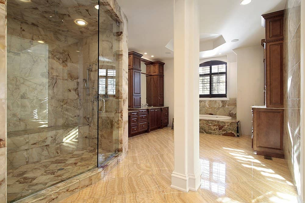 Large primary bathroom featuring beautiful flooring. It offers a large walk-in shower with stylish tiles flooring and walls. The drop-in soaking tub also has stylish tiles platform.