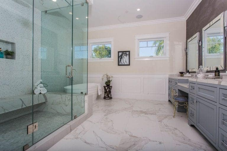 Primary bathroom featuring marble tiles flooring and a large walk-in shower room along with a freestanding tub. There are two sinks and a powder area as well.