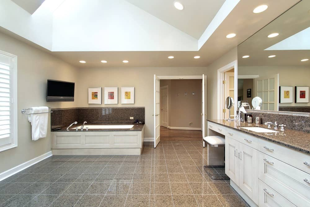 A spacious primary bathroom with stylish gray tiles flooring along with a ceiling with a skylight. The room offers a drop-in soaking tub with a widescreen TV on the wall, along with a powder desk and a granite sink counter.
