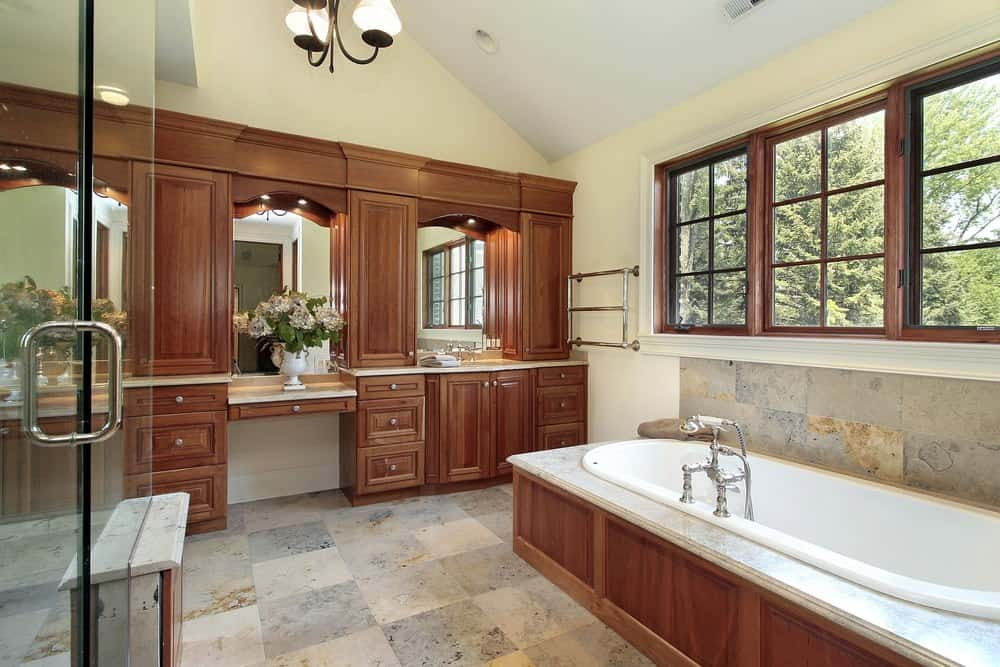 This primary bathroom features a sink counter and a powder desk with brown cabinetry. The room also has a drop-in soaking tub and a walk-in shower room. The space is lighted by a gorgeous ceiling light.