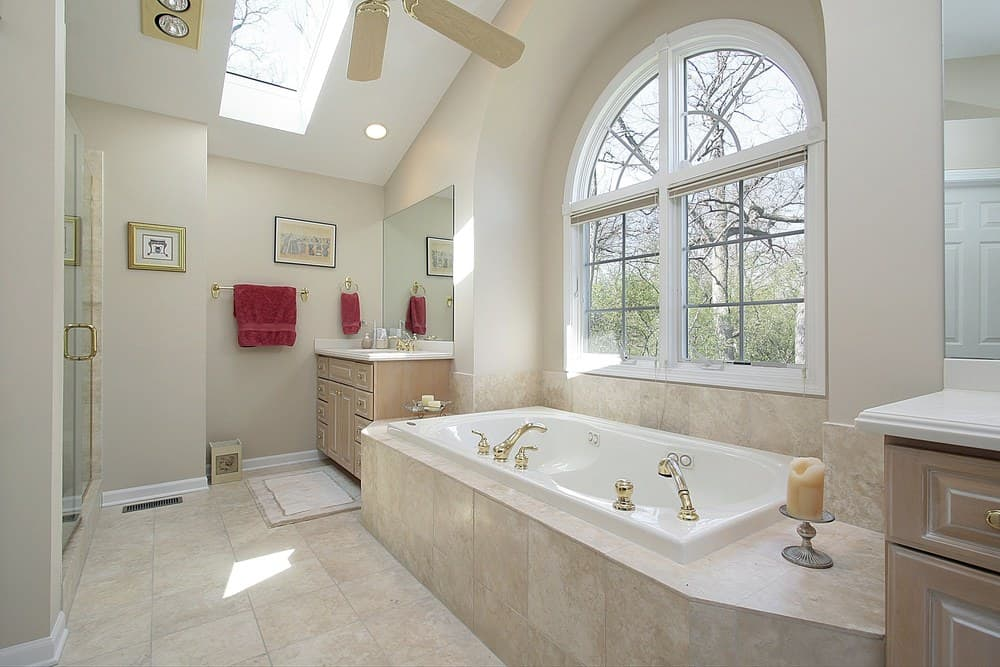 Large primary bathroom with a tall ceiling featuring a skylight. There's a walk-in shower area and a drop-in soaking tub by the windows.