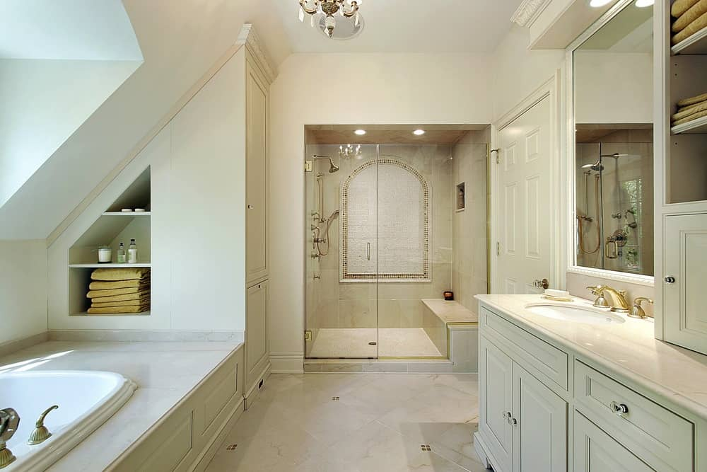 This primary bathroom offers a walk-in shower room along with a drop-in soaking tub with built-in shelving on the wall.