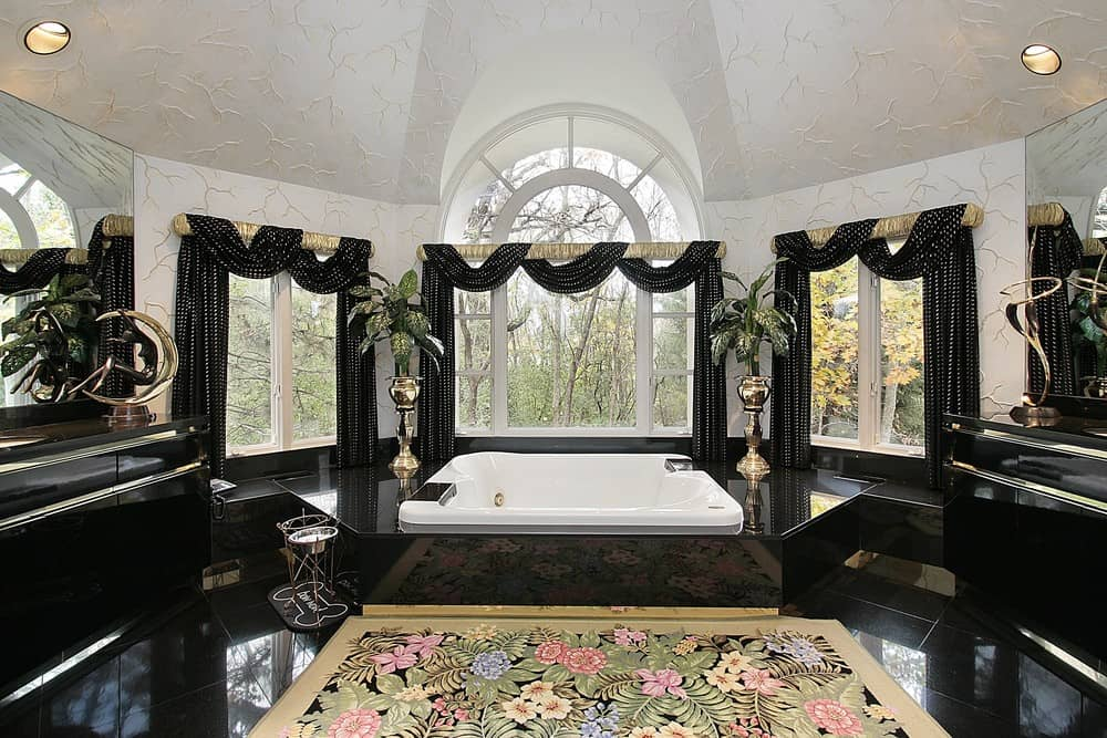 A glamorous primary bathroom with elegant black tiles flooring, black curtains and black sink counters, along with a drop-in tub with a black platform.