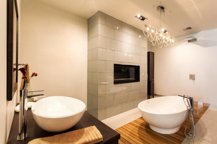 This modern primary bathroom offers a stylish freestanding tub that matches the vessel sink and is lighted by stunning ceiling lighting.