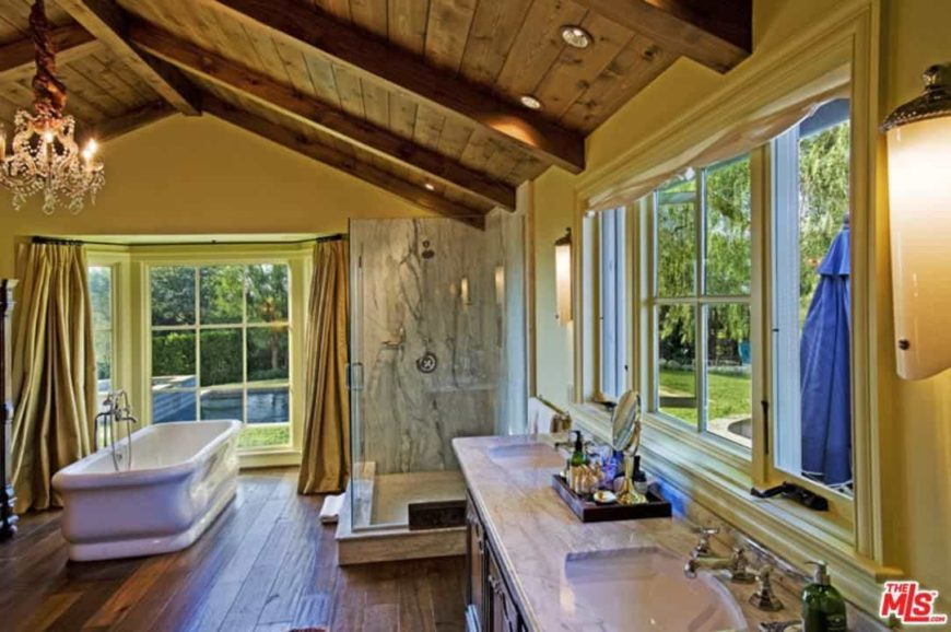 This primary bathroom features yellow walls and a wooden ceiling with exposed beams. The room is lighted by a glamorous chandelier. This bathroom offers a freestanding tub, a sink counter with two sinks and a walk-in shower area.