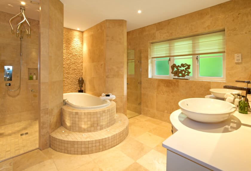 A classy primary bathroom featuring a drop-in soaking tub with tiles platform along with a walk-in shower room and a toilet room. The sink counter offers a pair of vessel sinks.