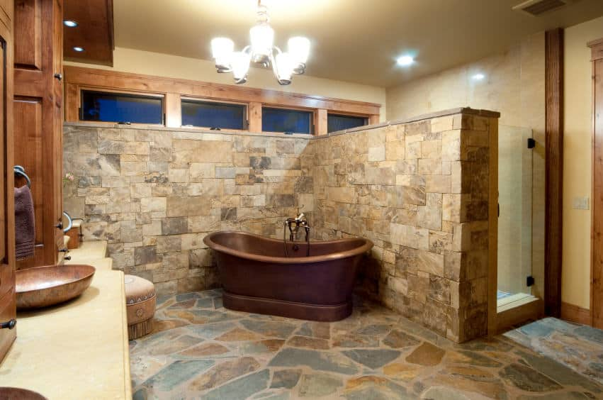 This primary bathroom boasts stone walls and floors. It has a bronze-finished freestanding soaking tub and a vessel sink, along with a walk-in shower room. The room is lighted by a gorgeous chandelier.