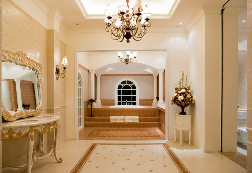 Large primary bathroom with classy tray ceiling lighted by glamorous chandeliers. The room features a charming double sink, a drop-in soaking tub and a walk-in shower and toilet room.