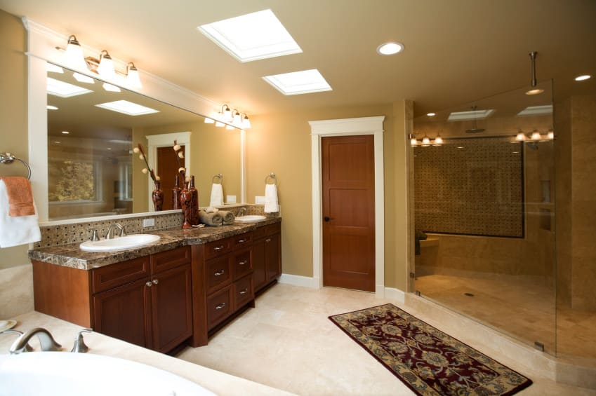 This primary bathroom features a sink counter with two sinks lighted by wall lights along with a drop-in soaking tub and a large walk-in corner shower room. The room also has two skylights.