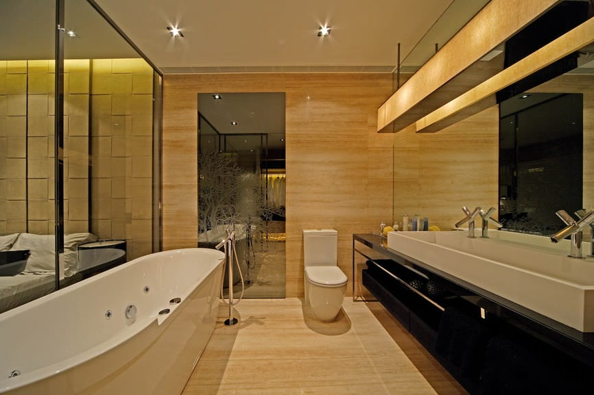 Modern primary bathroom boasting a large freestanding deep soaking tub along with a sink counter featuring a large vessel sink with two faucets.