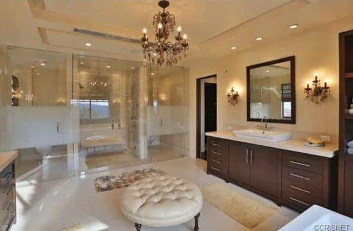A classy primary bathroom with two sink counters, a freestanding tub, a toilet room and a walk-in shower room. The room is lighted by a gorgeous chandelier.