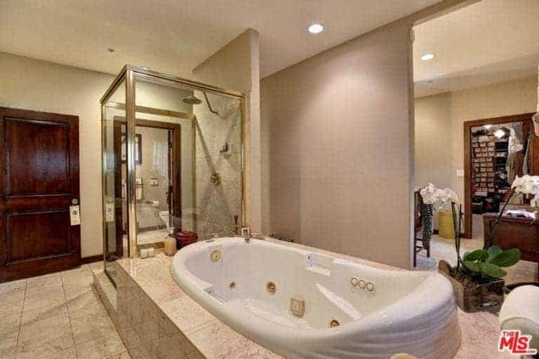 Primary bathroom featuring a deep soaking tub and a walk-in shower. There's a toilet room as well. This primary bathroom is connected to the home's walk-in closet.
