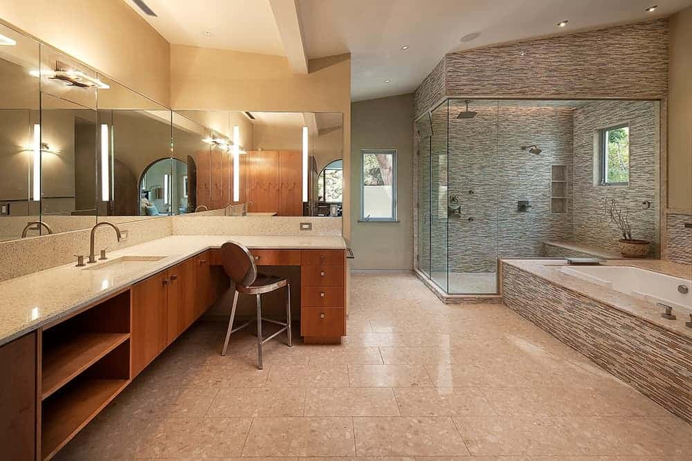 Large primary bathroom with tiles flooring. It features a sink counter and a powder desk. There's a drop-in tub and a walk-in shower area as well.