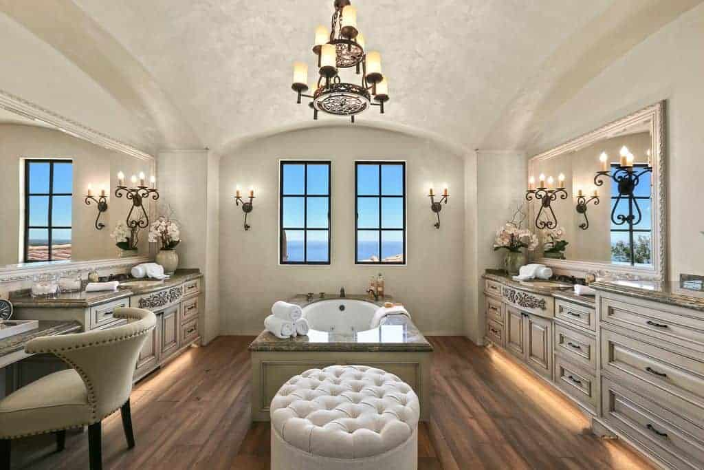 A spacious primary bathroom with a cathedral ceiling. It offers a drop-in tub in the middle and a couple of sink counters on both sides. There's a powder desk as well.