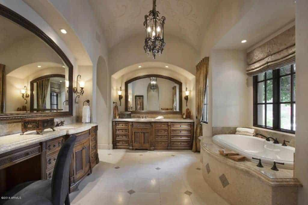 Spacious primary bathroom featuring sink counters and a powder desk lighted by classy wall lights. The room also has a deep soaking tub on the side.