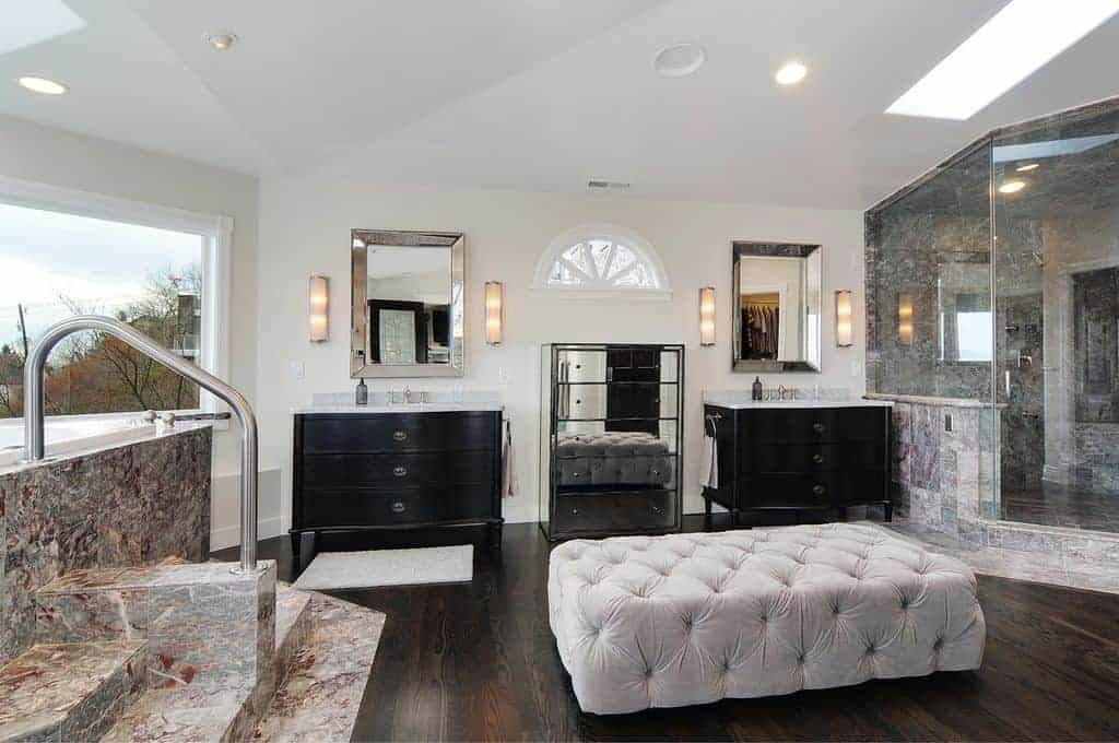White and spacious primary bathroom featuring a deep soaking tub and a large walk-in corner shower. There's an elegant ottoman and two sink counters. The room also features skylights.