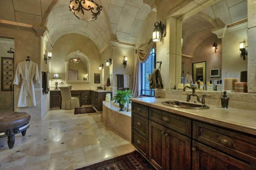 Large primary bathroom with a cathedral ceiling and tiles flooring. The room offers a powder desk, a sink counter, a drop-in tub and a walk-in shower room.