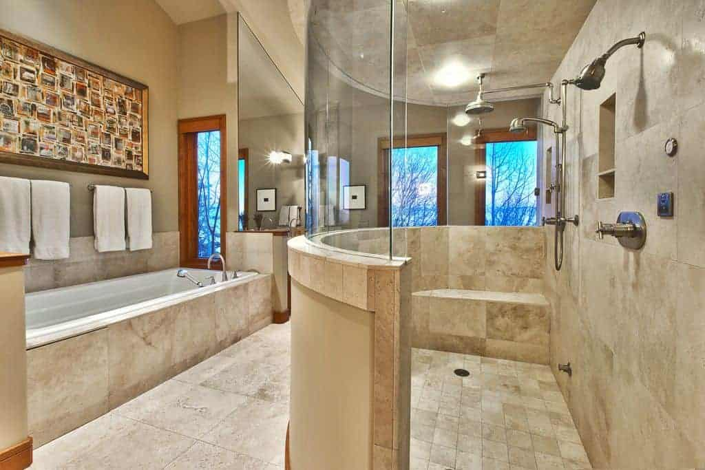 This primary bathroom offers a large walk-in shower space along with a long deep soaking tub on the side.