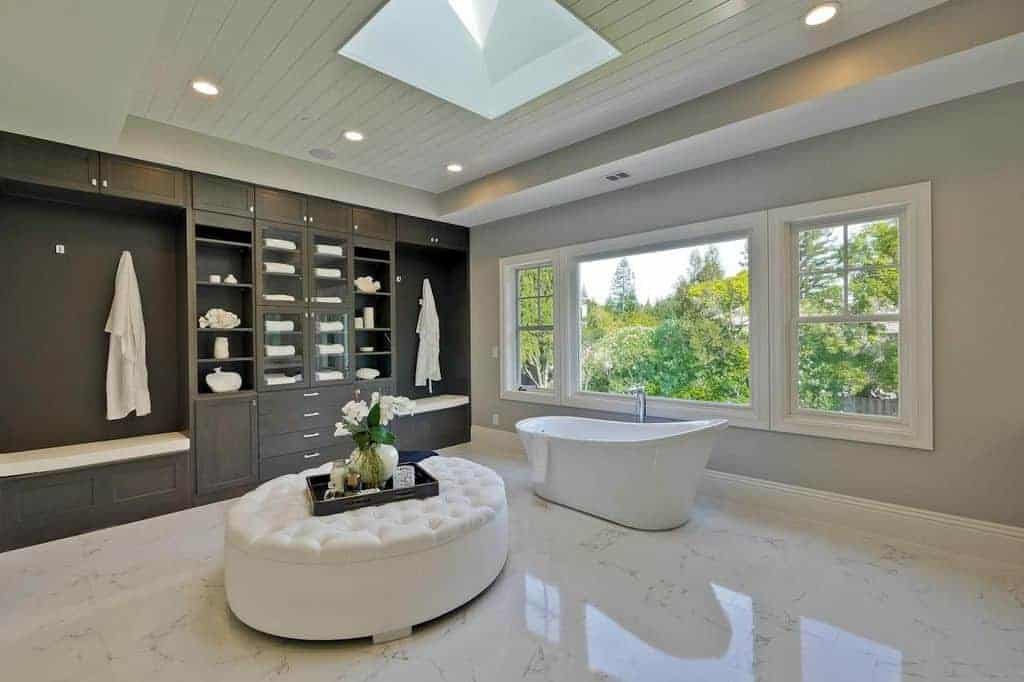 Spacious primary bathroom with sparkling tiles flooring and a skylight just above the large white ottoman. The room has cabinetry and shelving along with a freestanding tub by the windows.