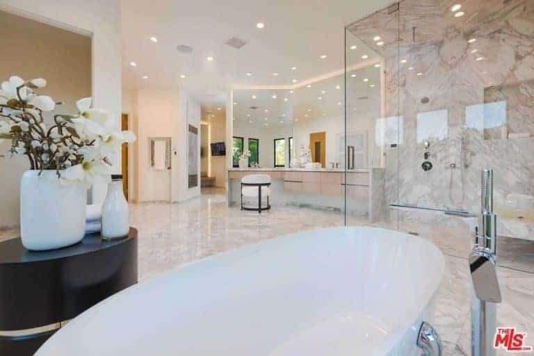 Large primary bathroom with tiles flooring and bright recessed lights. The room offers a powder desk, a walk-in shower room and a freestanding soaking tub.