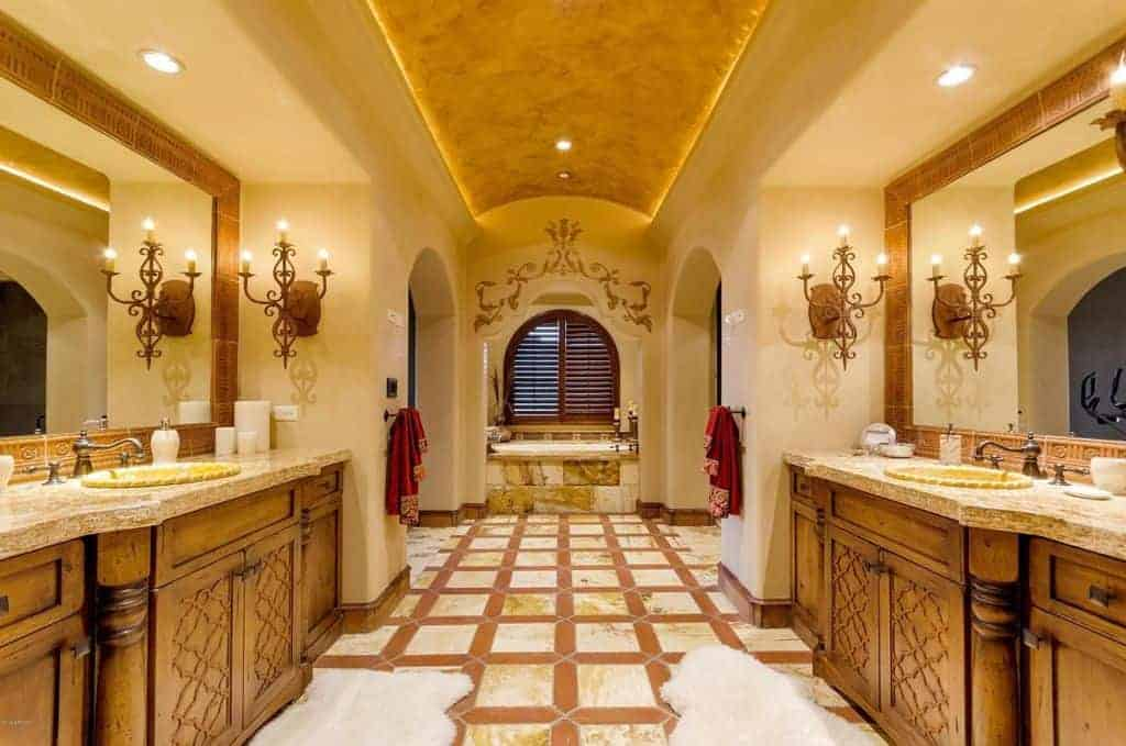 This primary bathroom boasts a beautiful ceiling and flooring, along with a decorated wall near the bathtub area. It also offers two sink counters lighted by classy wall lights.