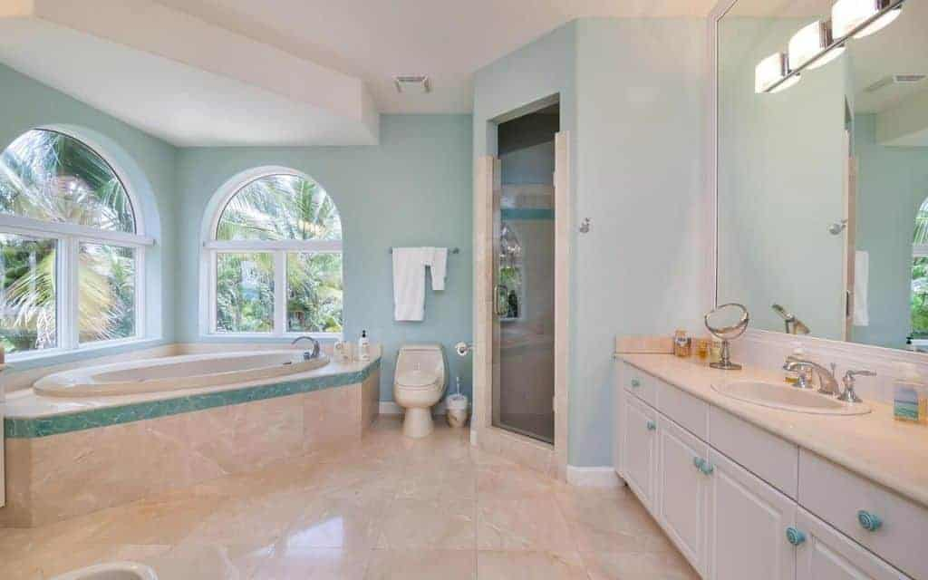 Green primary bathroom with beige tiles floors and beige sink counters. It has a walk-in corner shower room and a drop-in tub near the windows.