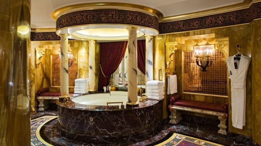 Luxurious primary bathroom with gold-finished walls and stunning tiles flooring. The flooring's design is so stunning while the bathtub's design is just so elegant.