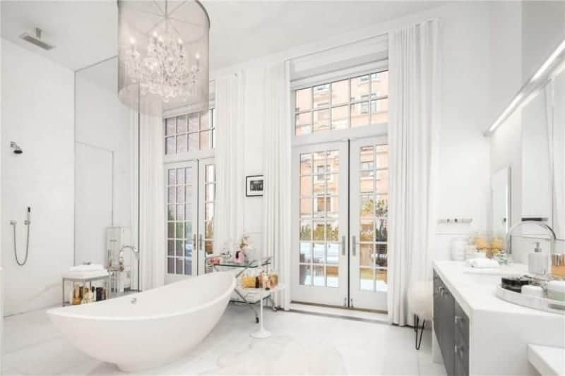 White primary bathroom featuring an open shower, a freestanding tub and a sink counter. The room is lighted by a gorgeous chandelier.